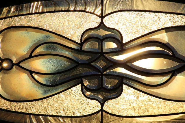 Artistic glass patterns on the front window of my parent's house, backlit by the setting sun.